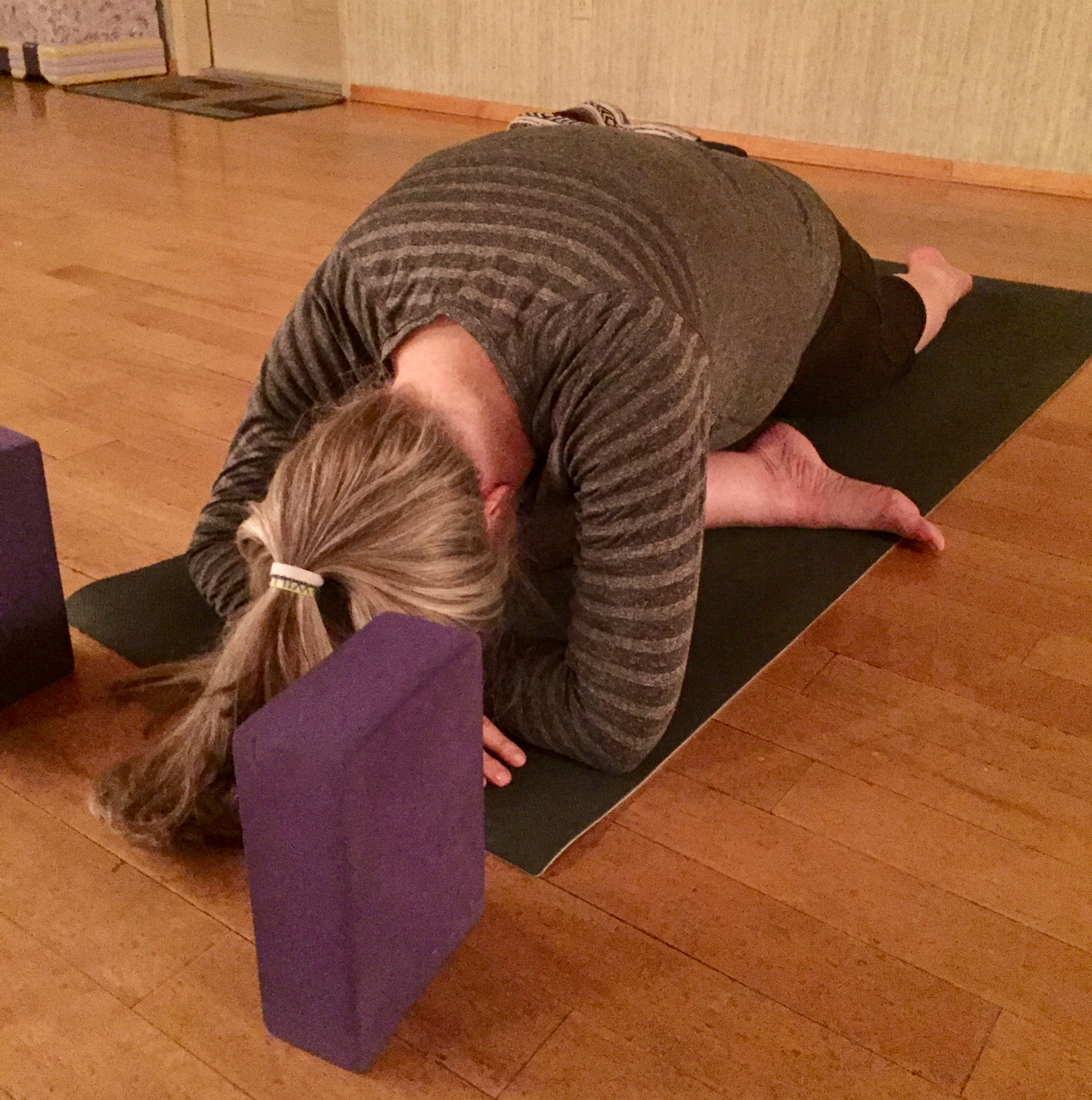 Stretching in Yoga Pigeon Pose to increase flexibility in knees and hips.